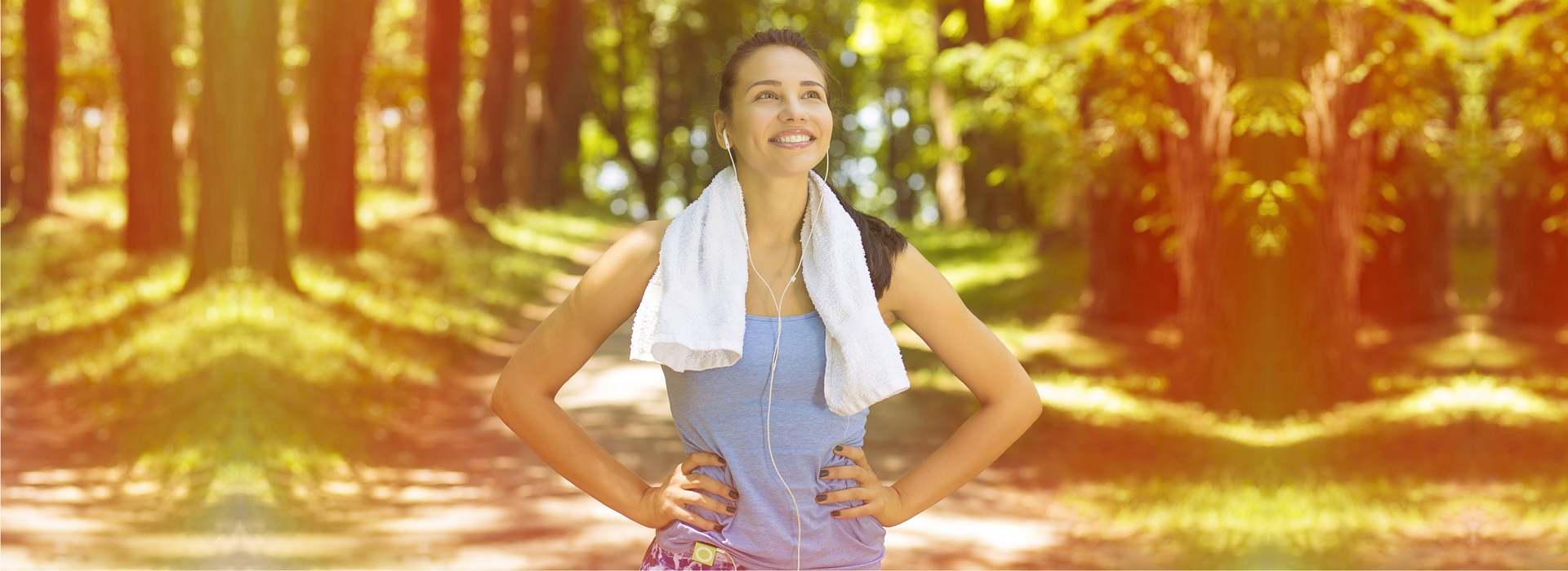 Fitness female standing happily in a forest