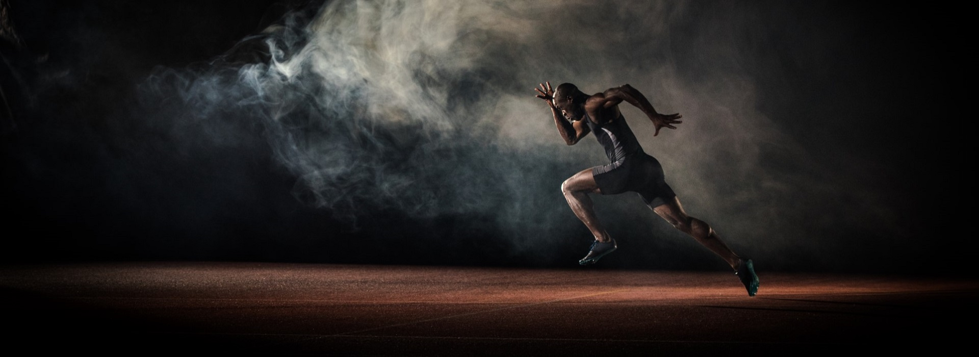 male sprinter in spot lit room with smoke sprinting