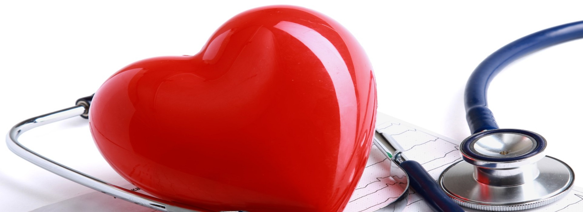 big red plastic heart with stethoscope and printed electrocardiograph
