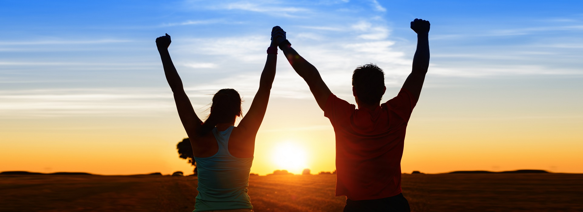 male and female holding hands raising arms together looking at the sunset