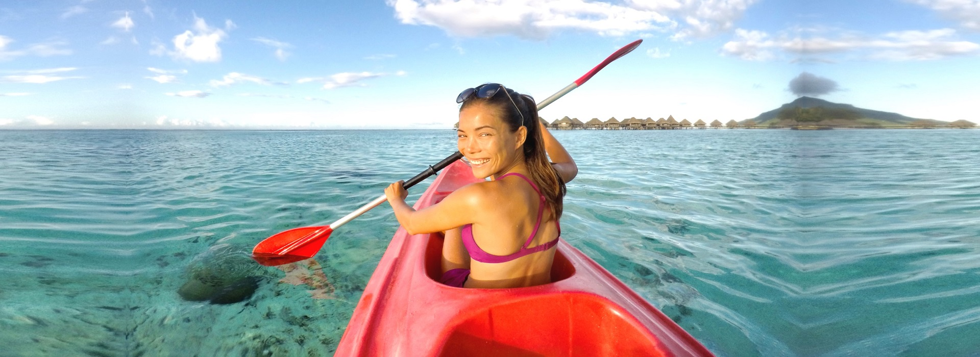 Keeping Fit While Holidaying Girl in red kayak paddling away looking over her head smiling