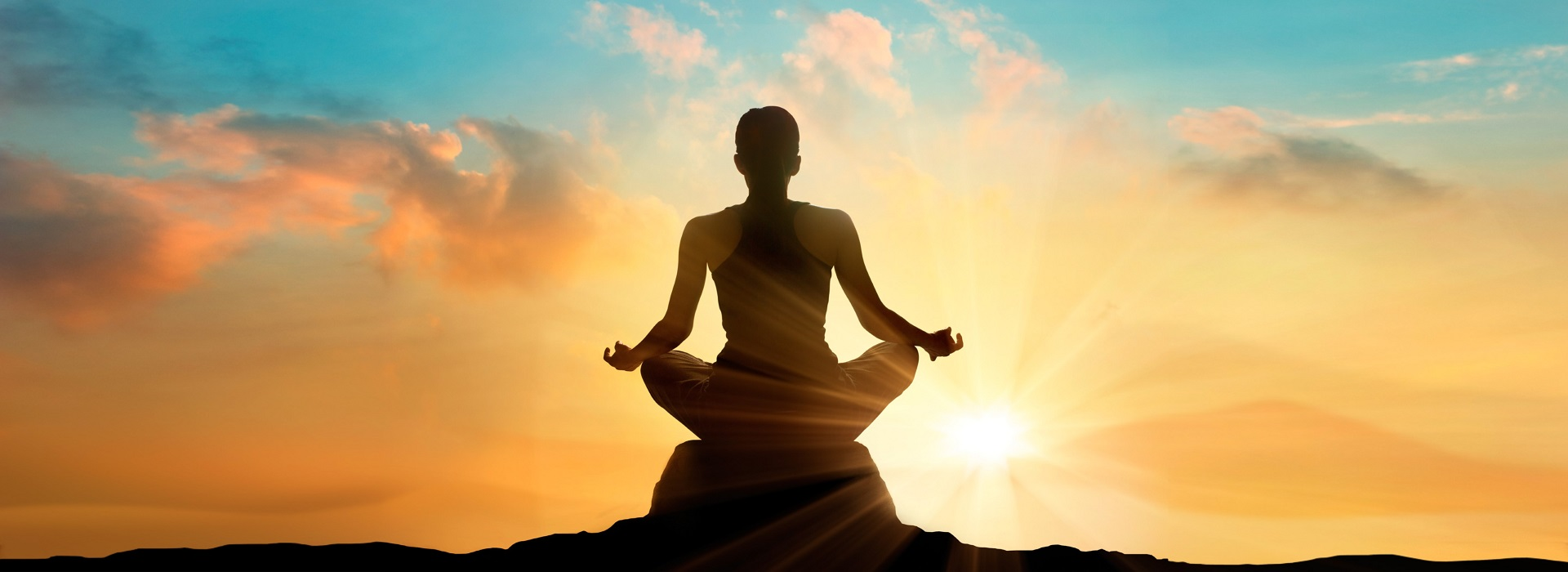 girl sitting on a rock with mountains in the background at sunset in meditation pose